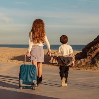 Niños de vista posterior caminando con equipaje
