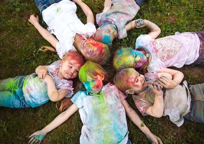 Los niños yacen sobre la hierba los niños pintados con los colores del festival holi yacen sobre la hierba