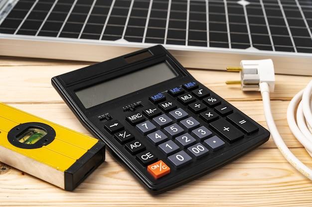 Nivel de construcción de la calculadora y panel solar en superficie de madera