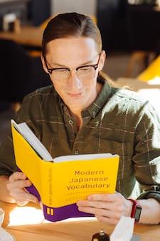 Nivel de idioma. agradable hombre inteligente sentado en la cafetería mientras estudia vocabulario japonés moderno