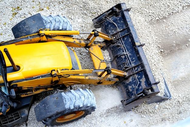 Niveladora amarilla, grava de carga para la construcción de carreteras
