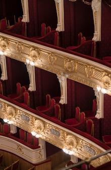 Niveles vacíos del balcón de la ópera con sillas rojas