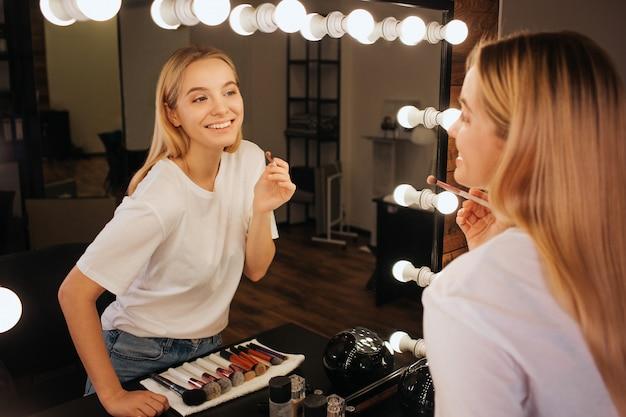 Niza alegre joven mira en el espejo en la sala de belleza y sonríe. ella sostiene el pincel para sombras de ojos.