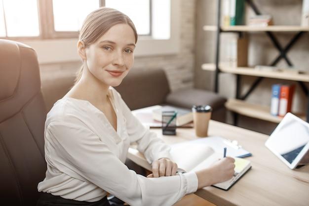 Niza joven empresaria plantean en la cámara. se sienta a la mesa en la sala y escribe en el cuaderno.