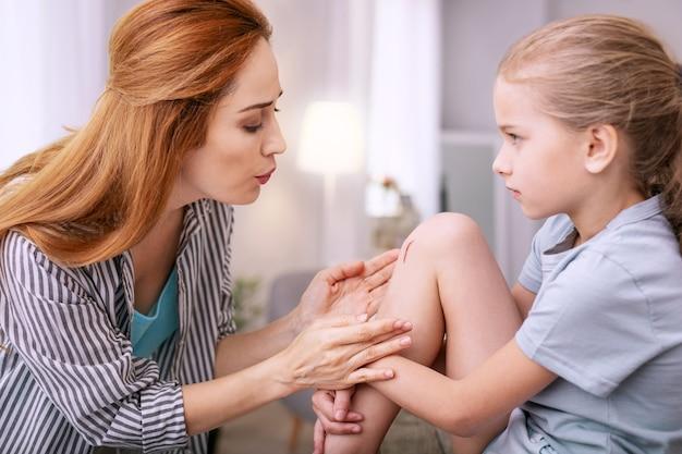 No dolera. agradable joven madre soplando en el rasguño mientras trataba de ayudar a su hija