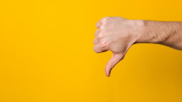 No es bueno y no está aprobado. cerrar la mano de un hombre mostrando el pulgar hacia abajo signo de disgusto con copyspace para el diseño