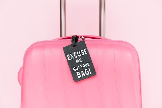 No la etiqueta de tu bolsa en la maleta de viaje rosa sobre fondo rosa
