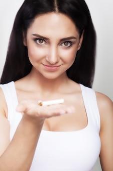 No fumar. el cigarrillo está roto en la mano de la niña.
