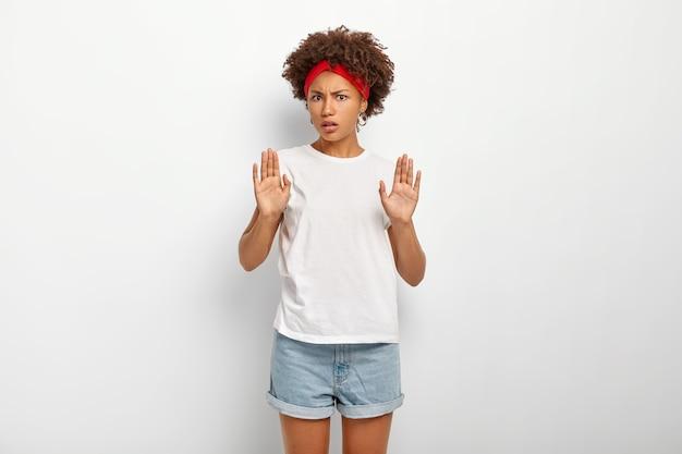 No, gracias. infeliz niña afroamericana disgustada hace gesto de parada, rechaza oferta