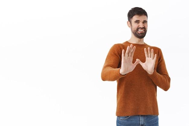 No, gracias, paso. retrato de hombre barbudo joven disgustado que hace muecas pidiendo mantenerse alejado, mantener la distancia, estrechar la mano en defensa y rechazo, retroceder para evitar algo repugnante