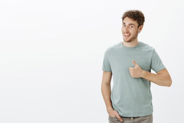 No he escuchado mejor las ideas. retrato de modelo masculino guapo positivo con cerdas en aretes, girando la cabeza de perfil y sonriendo ampliamente mientras muestra los pulgares hacia arriba
