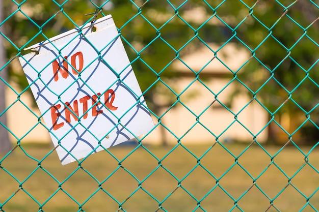 No ingrese letrero en la cerca verde de cerca al aire libre