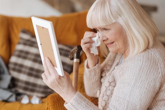 No llores. triste infeliz miserable mujer sosteniendo un pañuelo de papel y secándose las lágrimas mientras mira la fotografía