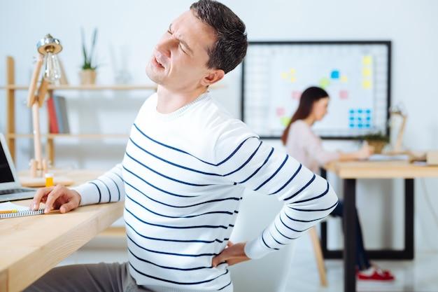 No lo toques. oficinista frustrado arrugando la frente y poniendo la mano izquierda en la espalda mientras está sentado en posición semi