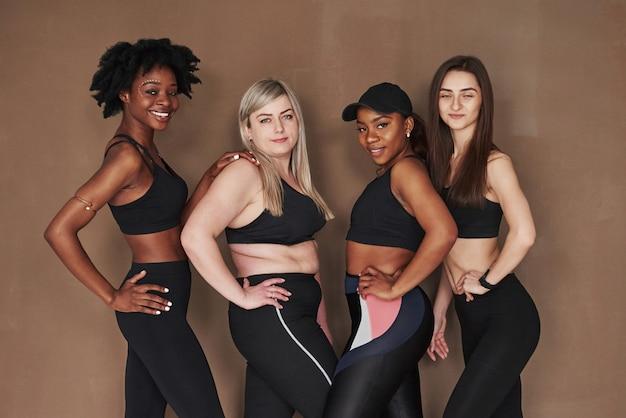 No parpadee por favor. grupo de mujeres multiétnicas de pie contra el espacio marrón