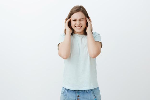 No puede soportar la presión durante la mitad del período. mujer intensa disgustada que sufre de dolor de cabeza, migraña apretando los dientes por el dolor y cerrando los ojos tomados de la mano en las sienes tratando de enfocar, desorientada