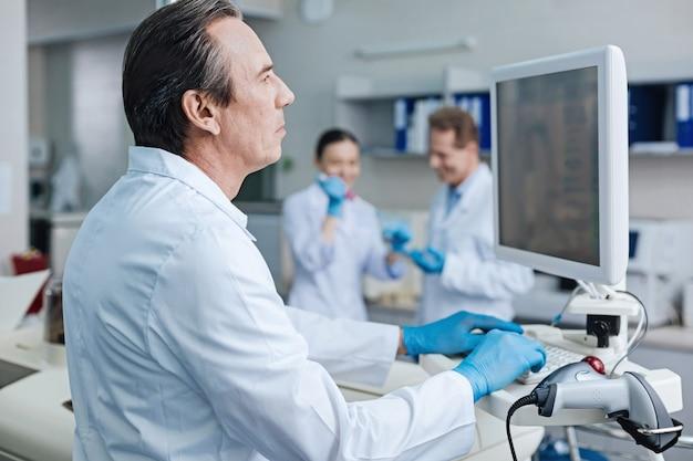 No te enojes. hombre atento vestido con uniforme médico y presionando los labios mientras analiza los resultados