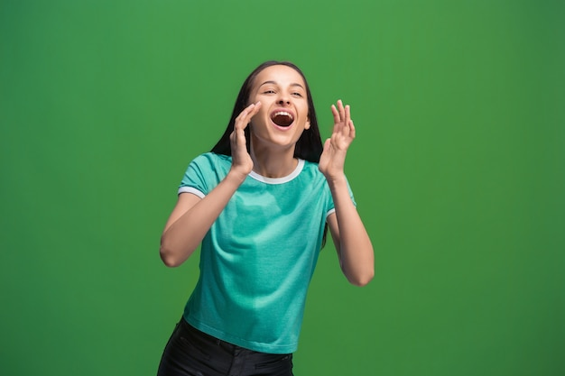 No te pierdas. joven mujer casual gritando. gritar. mujer emocional llorando gritando sobre fondo verde de estudio. retrato femenino de medio cuerpo. las emociones humanas, el concepto de expresión facial. colores de moda