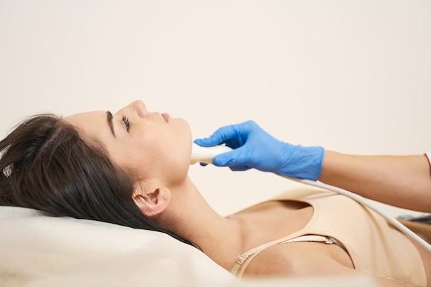 No te preocupes. trabajador médico competente que utiliza equipos modernos mientras controla las glándulas tiroides