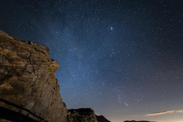 Noche en los alpes bajo el cielo estrellado y los majestuosos acantilados rocosos en los alpes italianos