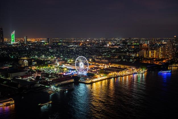 Noche en la ciudad de bangkok y vista al río chao phraya y noria en bangkok