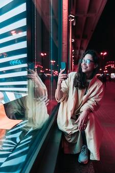 Noche en la ciudad, hermosa mujer entre luces rojas.