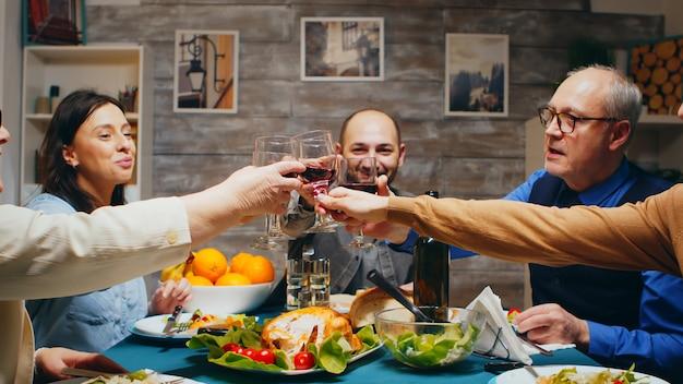 Por la noche, la familia se reunió para cenar tintineando copas de vino y brindando.
