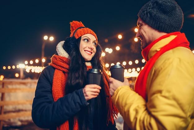 Noche de invierno, amor pareja bebe café al aire libre