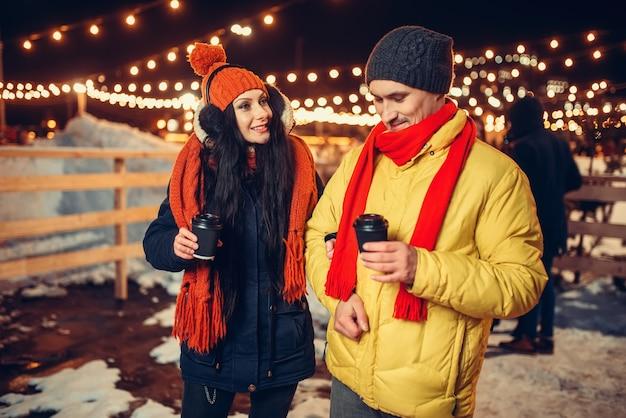 Noche de invierno, pareja camina con café al aire libre