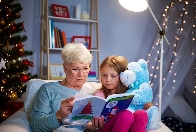 Noche de navidad con abuela, libro de cuentos y osito de peluche.