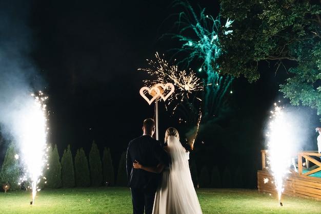 La noche de noche es el fondo. plan general de crecimiento. en la boda, los recién casados ven un hermoso saludo en el cielo.