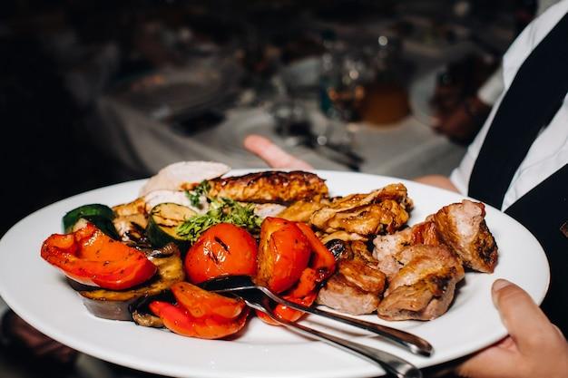 Por la noche, el restaurante sirve un plato caliente de barbacoa con verduras.
