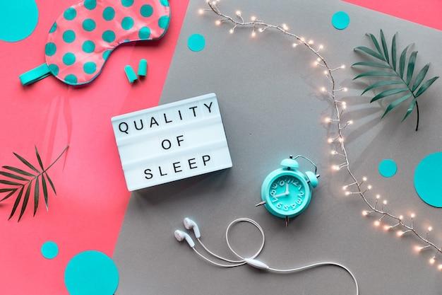Noche saludable sueño concepto creativo. máscara para dormir, despertador, auriculares, tapones para los oídos, píldoras y suplementos para dormir.