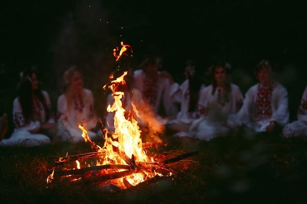 Noche de verano, jóvenes vestidos de eslavo sentados cerca de la hoguera.