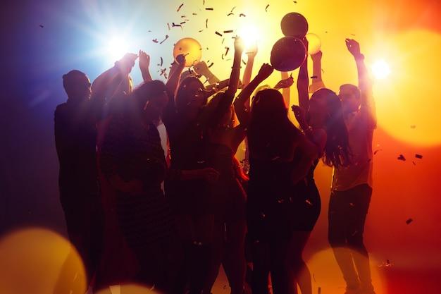Noches de verano. una multitud de personas en silueta levanta sus manos en la pista de baile sobre fondo de luz de neón. vida nocturna, club, música, baile, movimiento, juventud. colores amarillo-azul y niñas y niños en movimiento.