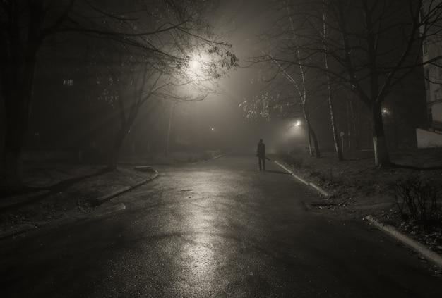 Noir silueta de un transeúnte en la calle de noche.