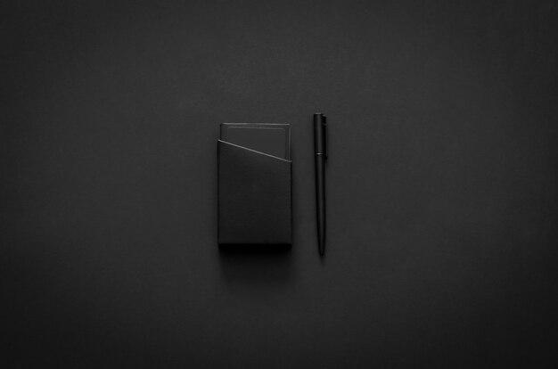 Nombre de la caja de la tarjeta y el bolígrafo en el estilo de vida moderno sobre fondo oscuro para el concepto negro minimalista endecha plana.