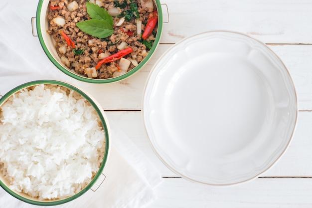 Nombre de la comida tailandesa pad ka prao, imagen de la vista superior de arroz con cerdo salteado con hojas de albahaca al lado de un plato vacío en la mesa de madera blanca