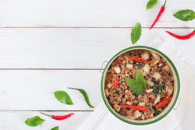 Nombre de la comida tailandesa pad ka prao, imagen de vista superior de cerdo salteado con hojas de albahaca en mesa de madera blanca