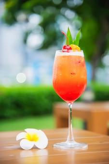 El nombre de la receta del cóctel mai tai o mai thai cóctel mundial incluye ron, jugo de limón, jarabe de orgeat y licor de naranja - bebida alcohólica dulce con flor en el jardín, concepto de vacaciones de relax
