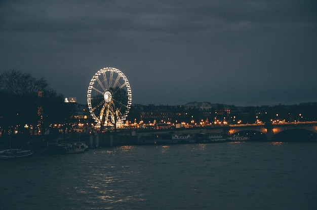 Noria rodeada por un río y edificios bajo un cielo nublado durante la noche en parís