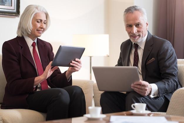 Nos gustan los gadgets. compañeros de edad sonrientes alegres que miran las tabletas y se sientan en la oficina mientras sostienen las tabletas y expresan alegría