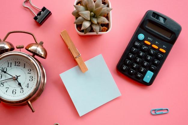 Nota adhesiva en blanco, calculadora, reloj sobre fondo rosa