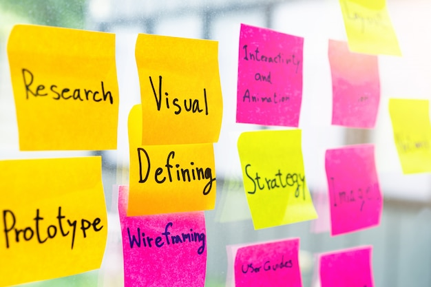 Nota adhesiva colorida en la pared de la oficina de vidrio con diseño gráfico relacionado con la palabra