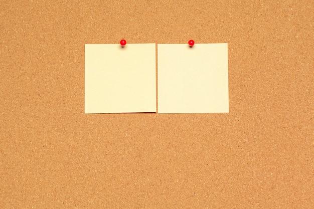 Nota adhesiva fijada en el tablero de corcho con chinchetas