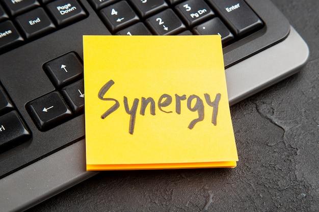 Nota adhesiva con la palabra synergy sobre el teclado