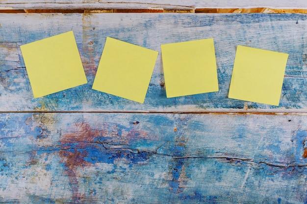 Nota amarilla de cuatro pegatinas en el fondo azul de madera vieja