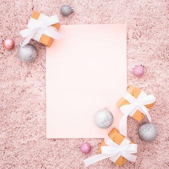 Nota en blanco con adornos navideños en una alfombra con textura rosa