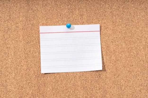 Nota en blanco blanco en un tablero de corcho para agregar texto y alfiler