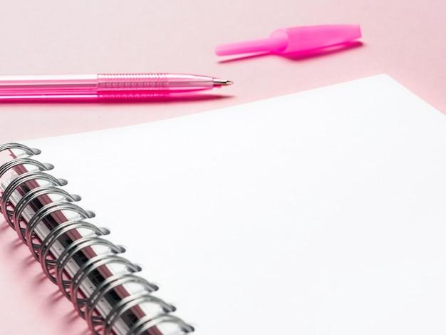 Nota en blanco con bolígrafo sobre fondo rosa